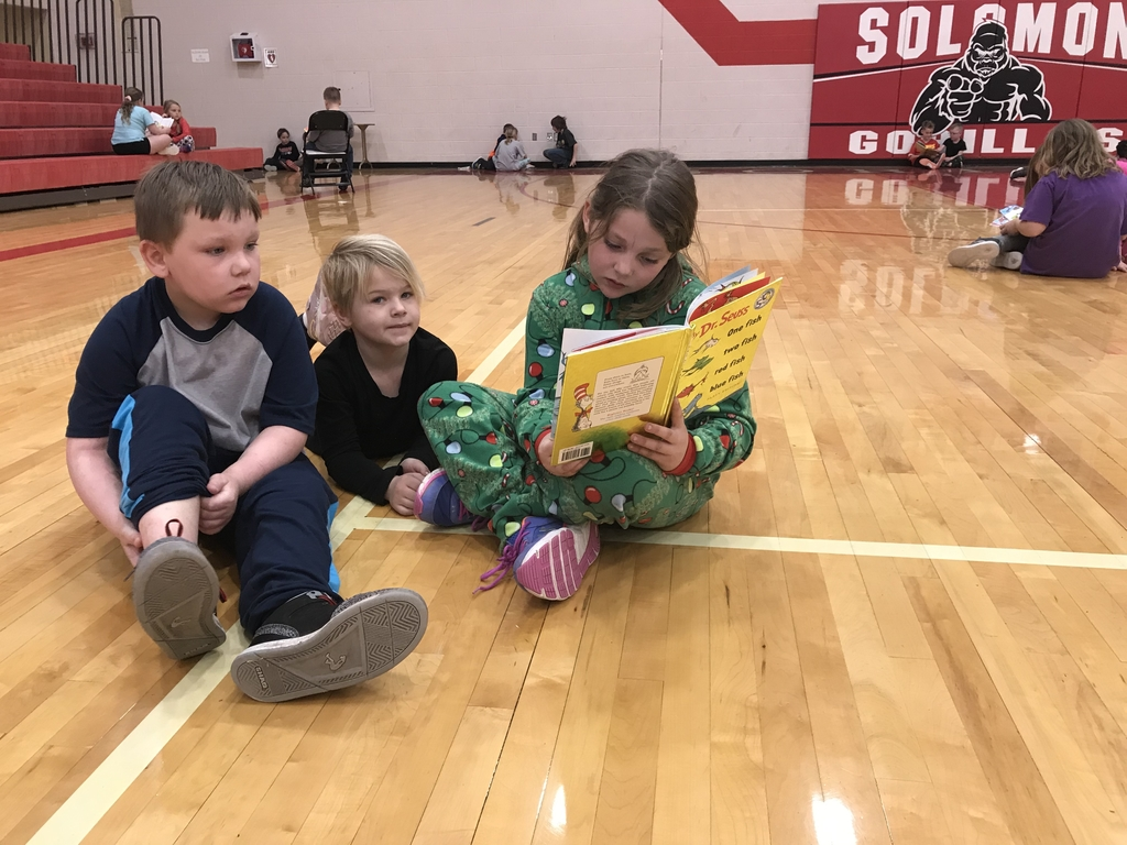 Aspen reads to kindergarten friends.
